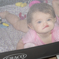 My lovely daughter, with her face smooshed against the play pen's screen.