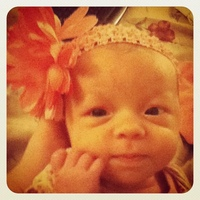 6 wks -- The cute flower headband someone gave her. The flower is like the size of her head!